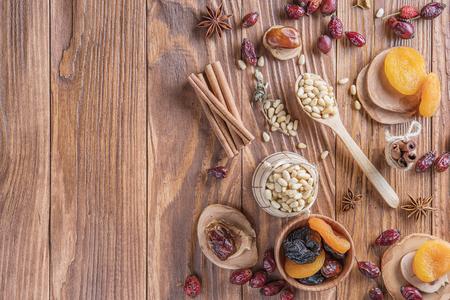 Mischung aus Nüssen, getrockneten Früchten, getrockneten Hagebutten und Gewürzen auf einem rustikalen hölzernen Hintergrund. Konzept des gesunden Snacks. Verschiedene Nüsse und getrocknete Früchte.