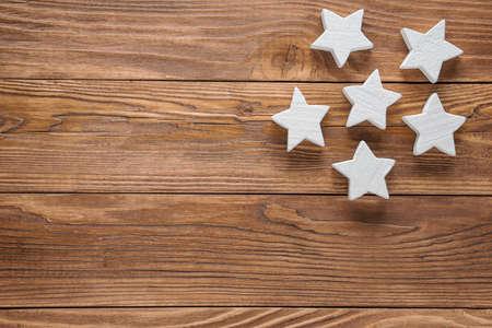 Weiße hölzerne Sterne auf braunem hölzernem Hintergrund, Kopienraum, Draufsicht.