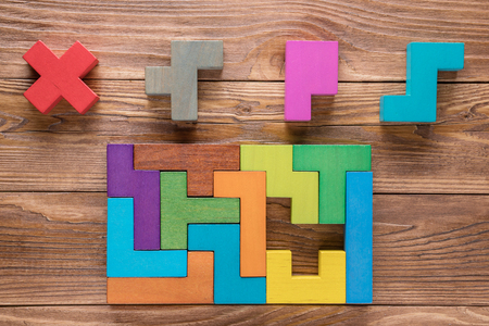IQ test. Choose correct answer. Logical tasks composed of colorful wooden shapes, top view. Childrens educational logical task, flat lay. Visual conundrum, find the missing piece of the proposed..