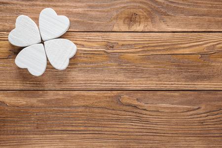 Abstrakter Klee auf hölzernem Hintergrund. Abstrakter weißer hölzerner Klee oder Schmetterling. Standard-Bild