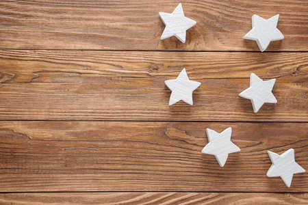 White wooden stars on brown wooden background, copy space, top view. Standard-Bild