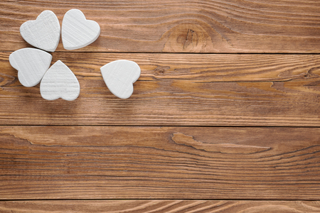 Abstract white flower on wooden background. One flower head on brown wood table background.  Fower with a torn petal.