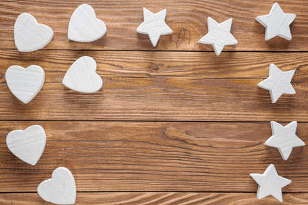 White wooden hearts and stars on brown wooden background, copy space, top view. Standard-Bild