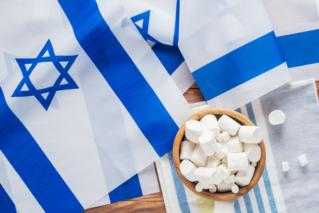 Israel national flags and marshmallows on a wooden background, top view, flat lay.