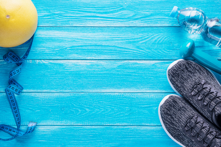 Set for sports activities on blue wooden background. Sport equipment, yoga mat, sport shoes, measuring tape, dumbbell, hand expander, sweetie fruit and bottle of water.