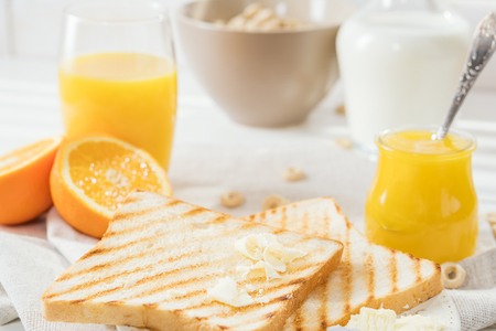 Delicious breakfast, french toasts with butter and honey, fresh oranges and juice.