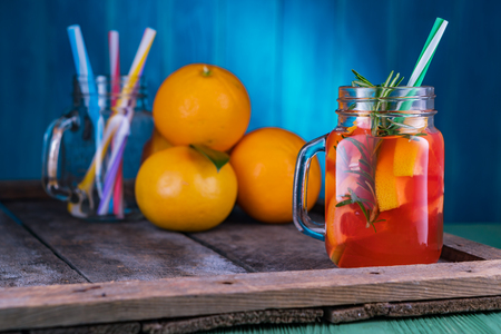 Cocktail with grapefruit and rosemary, long drink. Pink cocktail in mason jar bottle on old dark rustic background. Stockfoto