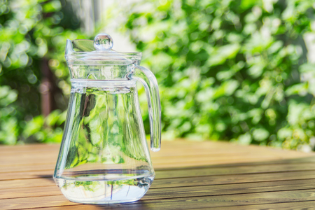 Pitcher with water on the wooden table against green foliage background. Jug on a green outdoor background. Copy space. Standard-Bild - 104353112