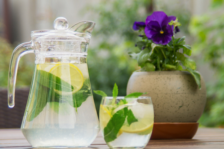 Fresh homemade lemonade with ice and mint on the table with copy space. Standard-Bild - 104353110
