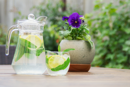 Fresh homemade lemonade with ice and mint on the table with copy space. Standard-Bild - 104353113