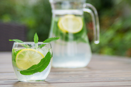 Fresh homemade lemonade with ice and mint on the table with copy space. Standard-Bild - 104353117