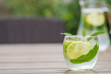 Fresh homemade lemonade with ice and mint on the table with copy space. Standard-Bild - 104353120