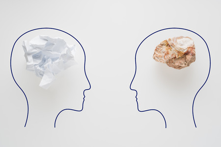 Heads of two people with crumpled paper brain shape and stone brain shape. Two people with different thinking. Rational and irrational thinking. Idea and teamwork. Creative business concept. Standard-Bild - 106354219