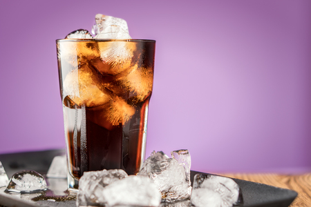 Cola with ice cubes and bubbles in glass on lilac background. Standard-Bild - 106385431