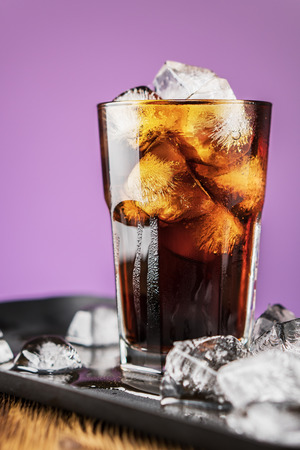 Cola with ice cubes and bubbles in glass on lilac background. Standard-Bild - 106385542
