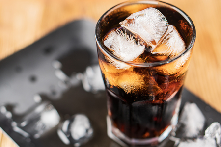 Cola with ice cubes and bubbles in glass, top view. Standard-Bild - 106385548
