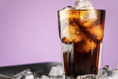Cola with ice cubes and bubbles in glass on lilac background. Standard-Bild - 106385632