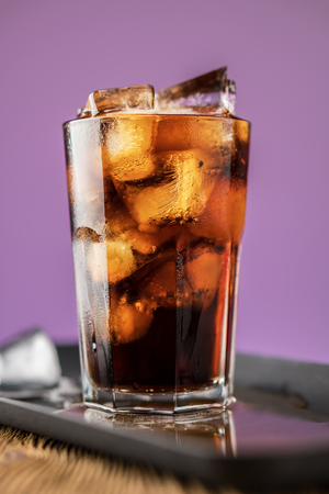 Cola with ice cubes and bubbles in glass on lilac background. Standard-Bild - 106385638