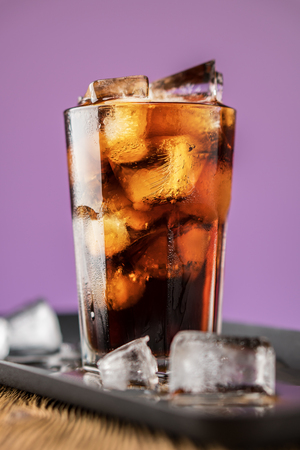 Cola with ice cubes and bubbles in glass on lilac background. Standard-Bild - 106385660