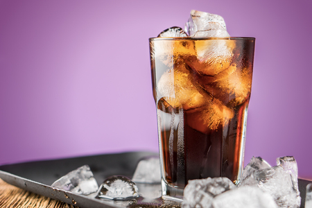 Cola with ice cubes and bubbles in glass on lilac background. Standard-Bild - 106385696