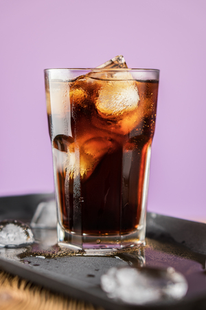 Cola with ice cubes and bubbles in glass on lilac background. Standard-Bild - 106385697
