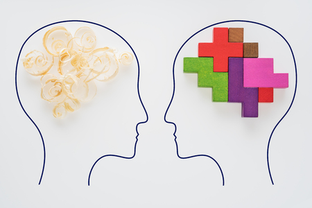 Heads of two people with sawdust brain shape and colorful geometric shape. Two people with different thinking. Rational and irrational thinking. Idea and teamwork. Standard-Bild - 106385726