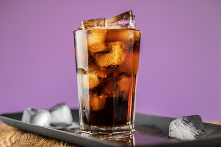 Cola with ice cubes and bubbles in glass on lilac background. Standard-Bild - 106385728