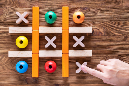 Wooden  tic tac toe (OX) game. The concept of strategy, risk, competition in business.  Woman playing a game of tic tac toe