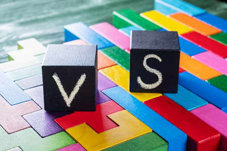 Letters VS on colorful wooden background with copy space. The concept of making choice. Versus concept. Black cubes with letters VS. Banque d'images - 121430414