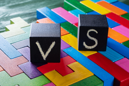 Letters VS on colorful wooden background with copy space. The concept of making choice. Versus concept. Black cubes with letters VS. Banque d'images - 121430415