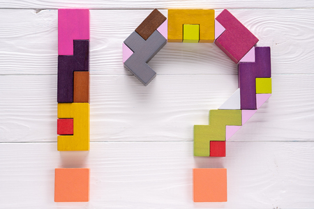 Exclamation point and a question mark from colorful wooden blocks on white wooden background.