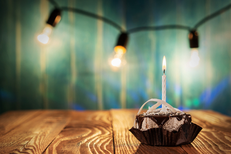 Delicious birthday cupcake with candle on table on blue background with light bulbs.