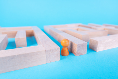 People in the maze, finding a way out. The man in the maze. The concept of a business strategy, analytics, search for solutions, the search output. Labyrinth of wooden blocks.