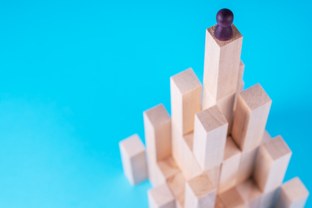 Abstract construction from wooden blocks with copy space on blue background. Business metaphor, abstract person on top of a career. The concept of success, achievement, victory.