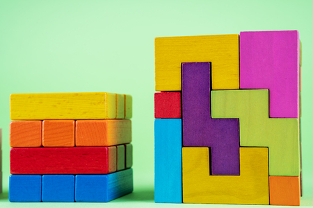 Growing graph from wooden cubes on green background. The concept of financial growth, progress, development. Cubes of wooden multi-colored blocks. Foto de archivo