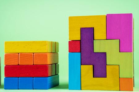 Wachsendes Diagramm aus Holzwürfeln auf grünem Hintergrund. Das Konzept des Finanzwachstums, des Fortschritts, der Entwicklung. Würfel aus bunten Holzblöcken. Standard-Bild