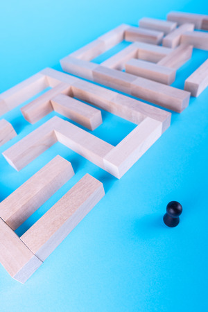 People in the maze, finding a way out. The man in the maze. The concept of a business strategy, analytics, search for solutions, the search output. Labyrinth of wooden blocks. 免版税图像