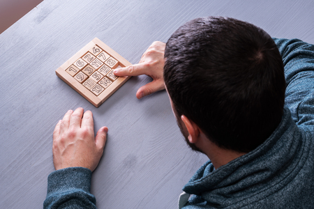 Top view on man's hand solves the conundrum on the gray wooden table background, close up. The concept of concentration, logical thinking.