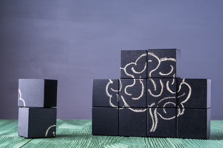 The concept of the human brain. Education, science and medical concept.  Brain drawn in chalk on black cubes.