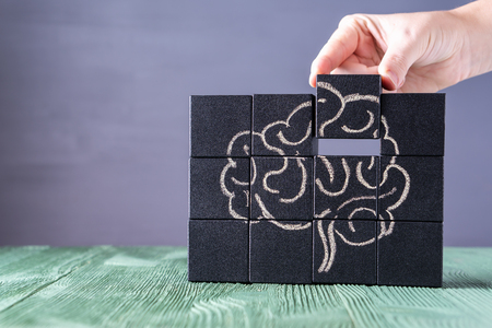 The concept of the human brain. Education, science and medical concept.  Brain drawn in chalk on black cubes. Female hands put in place the last element of the puzzle. 스톡 콘텐츠