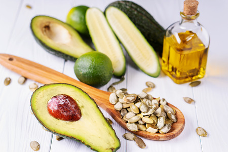 Avocado, cucumber, lime, pumpkin seeds and oil on a white wooden table, healthy food. Healthy lifestyle concept, diet.