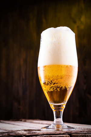 Cold beer into a glass with  foam, close up.