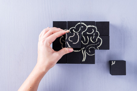 The concept of the human brain. Education, science and medical concept.  Brain drawn in chalk on black cubes. Female hands put in place the last element of the puzzle.
