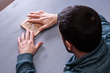 Top view on mans hand solves the conundrum on the gray wooden table background, close up. The concept of concentration, logical thinking.