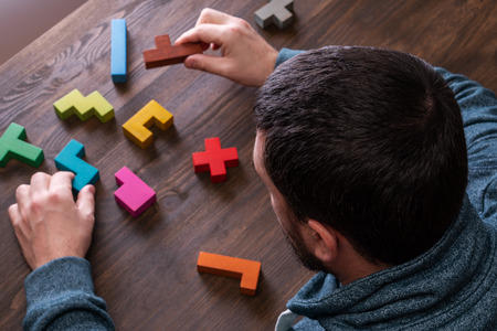 A man connects different geometric shapes, the concept of concentration, logical thinking. Top view on mans hand playing with colorful wooden blocks on the brown wooden table background.