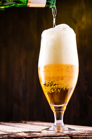 Cold beer is pouring into a glass forming foam, close up.