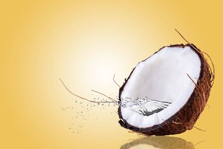 Coconut with splashes of water. Half coconut on yellow background.