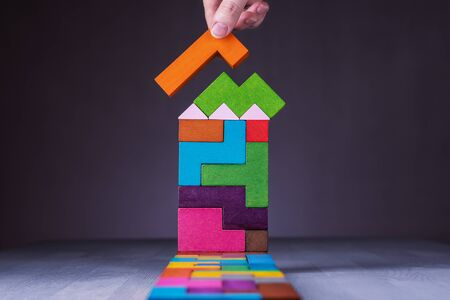 Abstract house of wooden puzzles. Business concept, sale, mortgage, rent. Female hand holding wooden block. Building house.