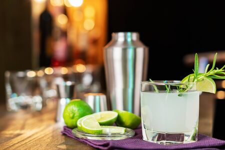 Lime cocktail with rosemary on the background of the bar. Refreshing alcoholic cocktail.