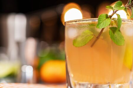 Fresh cocktail with lime, mint and ice on the background of the bar. Refreshing alcoholic cocktail. Close up.